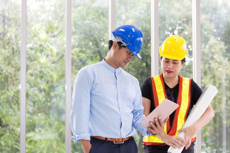Dwa inżyniera pracuje pokój konferencyjnego z pastylką Dwa pracownika oglądają budowa plan przy biurem Elektryka carpente obrazy royalty free