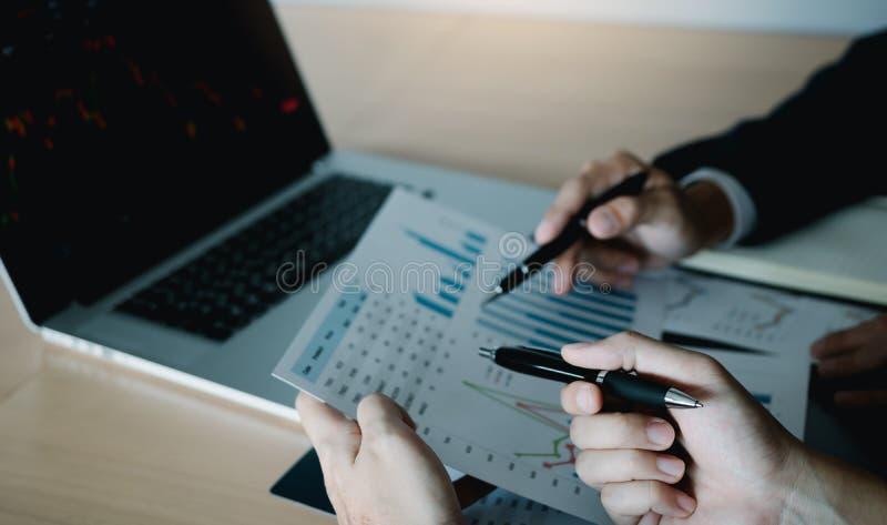 Dwa inwestora pracuj? wraz z analizowa? akcyjnych dane wykresy w papierze i przegl?da? dane na laptopu ekranie zdjęcia stock