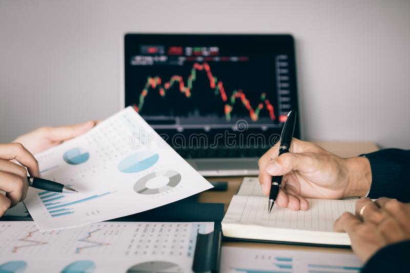 Dwa inwestora pracuj? wraz z analizowa? akcyjnych dane wykresy w papierze i przegl?da? dane na laptopu ekranie fotografia stock