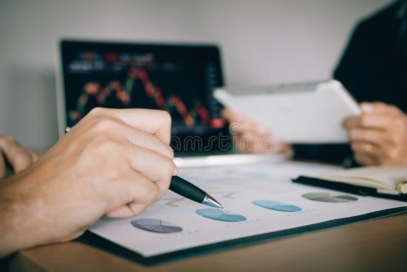 Dwa inwestora pracuj? wraz z analizowa? akcyjnych dane wykresy w papierze i przegl?da? dane na laptopu ekranie zdjęcia royalty free