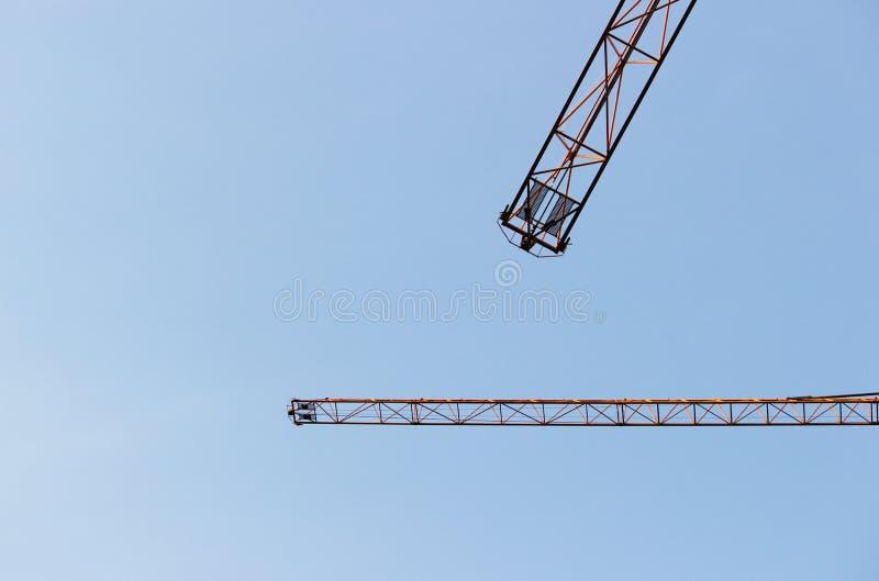 dwa jib żurawia przeciw bezchmurnemu niebieskiemu niebu royalty ilustracja