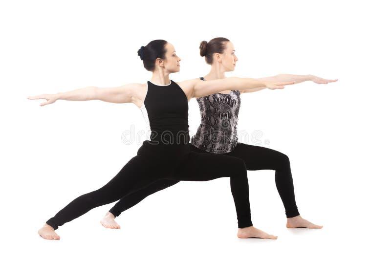 Dwa jog dziewczyny stoi w joga wojownika II pozie zdjęcia stock