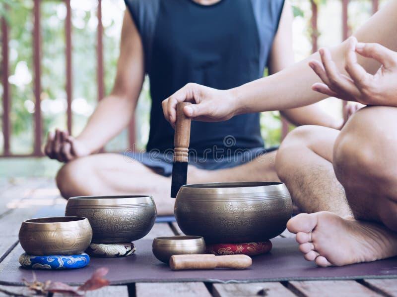 Dwa joga mężczyzna robią joga plenerowy z śpiewów pucharami zdjęcie royalty free
