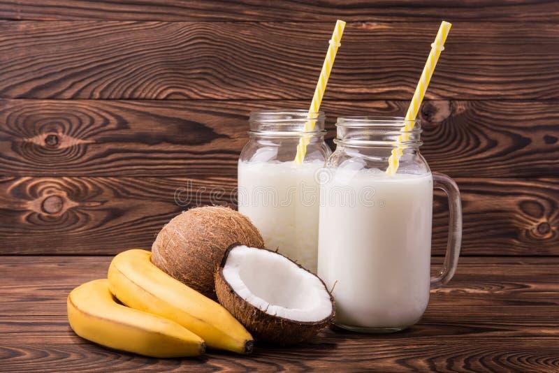 Dwa kamieniarza przejrzysty słój pełno kokosowy mleko na ciemnego brązu drewnianym tle Soczyści żółci banany i koks blisko słoju zdjęcia stock