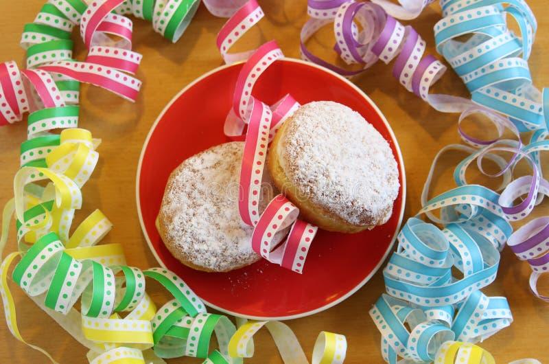 Dwa karnawałowego donuts na talerzu z wielo- barwionym streame zdjęcia stock