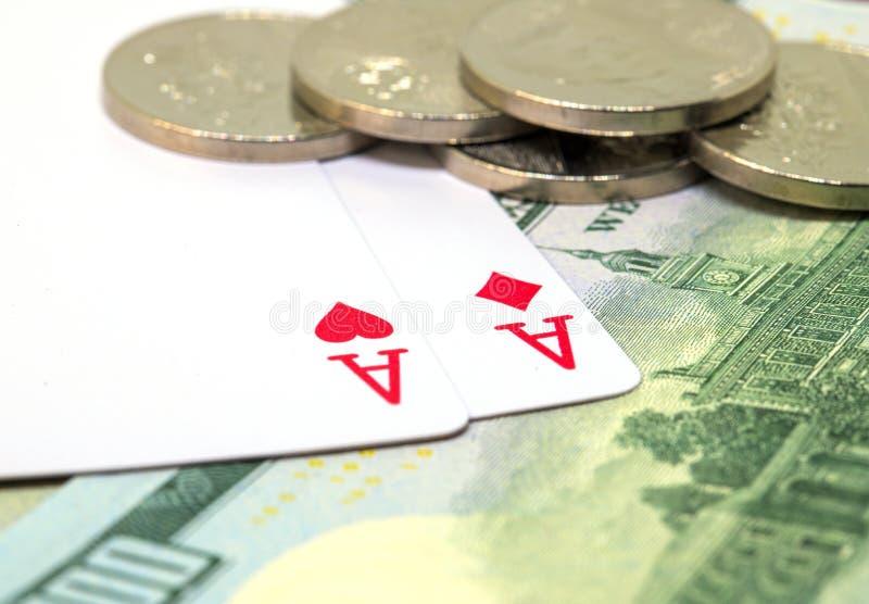Dwa karta do gry, banknoty i monety, ręka w pokera zwycięstwo Serca i karowy as na stole obrazy stock