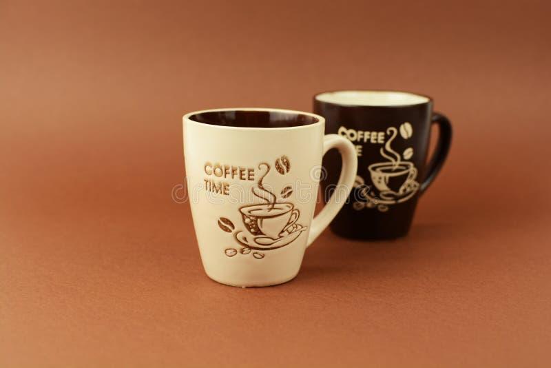 Dwa kawowej czas filiżanki na brown tle zdjęcie stock