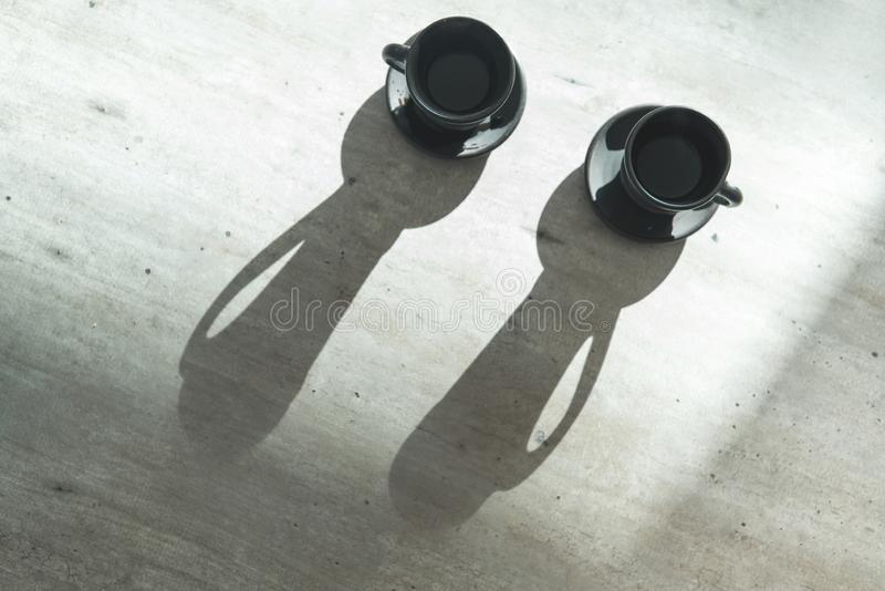 Dwa Kawowej glinianej czarnej filiżanki na stole z jaskrawym backlight który rysuje długa filiżanka ocieniają Kawa dla pary w now zdjęcie stock