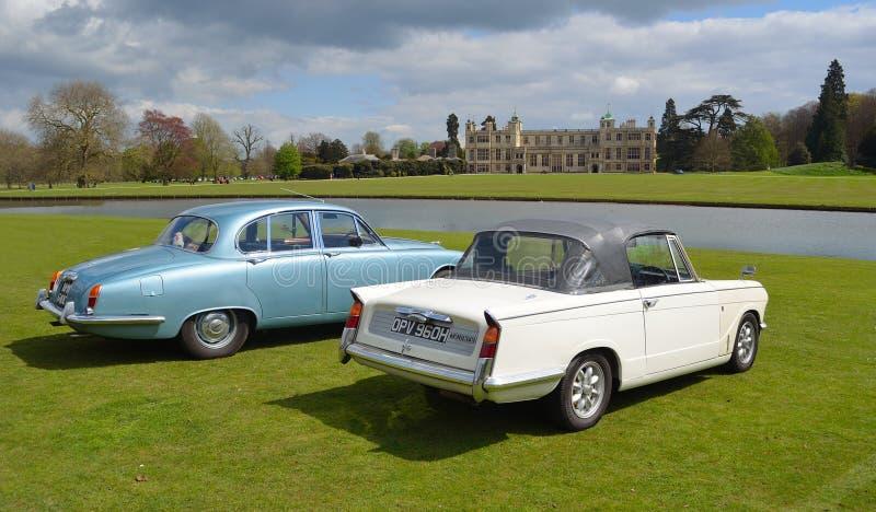 Dwa Klasycznego samochodu przed dostojnym domem, Triumph Herald kabrioletem i Jaguar, obraz stock