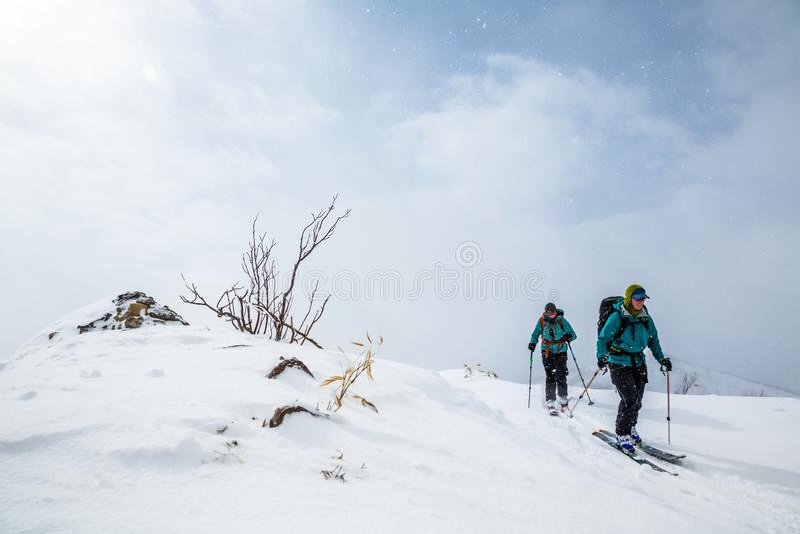 Dwa kobiet backcountry narciarstwo, wycieczkuje wierzchołek szczyt w hokkaido, Japonia obrazy stock