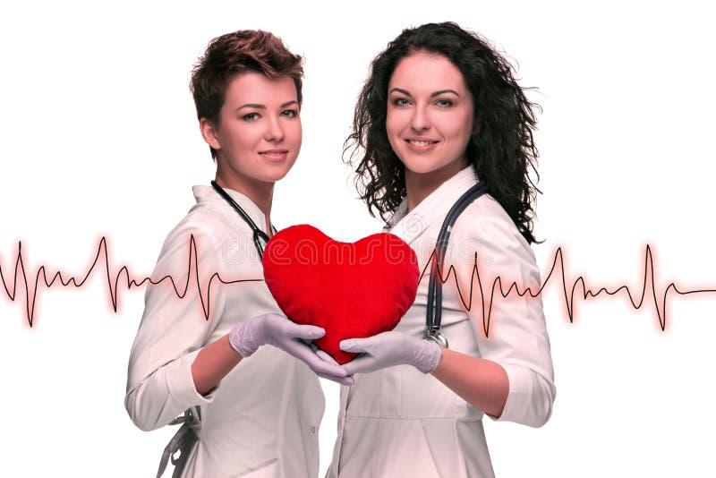 Dwa kobiet doktorski mienie czerwony serce zdjęcie stock