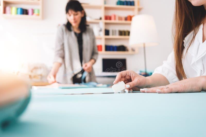 Dwa kobiet krawcowa robi projektant odzieży w sala wystawowej Młoda żeńska fachowa szwaczka pracuje przy szyć zdjęcie stock