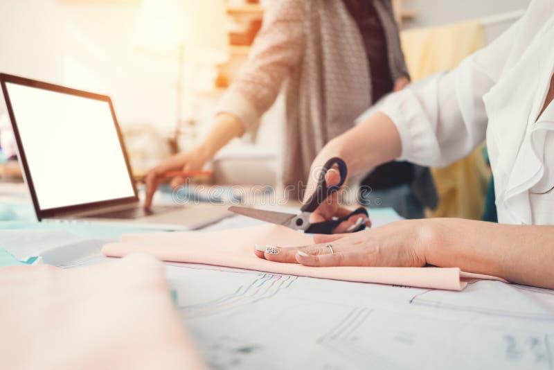 Dwa kobiet krawcowa robi projektant odzieży w sala wystawowej Młoda żeńska fachowa szwaczka pracuje przy szyć zdjęcia stock