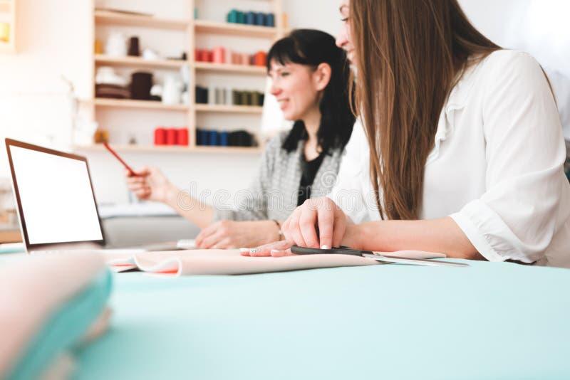Dwa kobiet krawcowa rozwija i robić nowej koncepci odzieży z nowożytnym laptopem obrazy royalty free