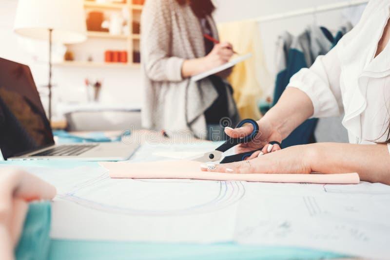 Dwa kobiet krawcowa rozwija i robić nowej koncepci odzieży z nowożytnym laptopem obraz stock