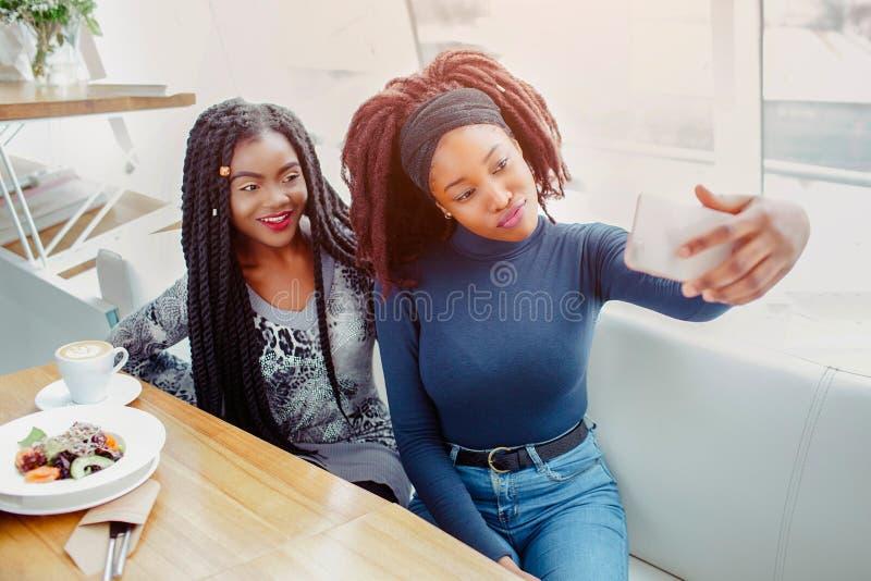 Dwa kobiet młoda afrykańska poza na telefon kamerze Biorą selfie Modele siedzą przy stołem w kawiarni zdjęcie royalty free