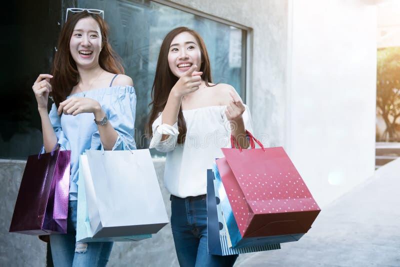 Dwa kobiet młody szczęśliwy azjatykci robić zakupy plenerowy zdjęcia stock