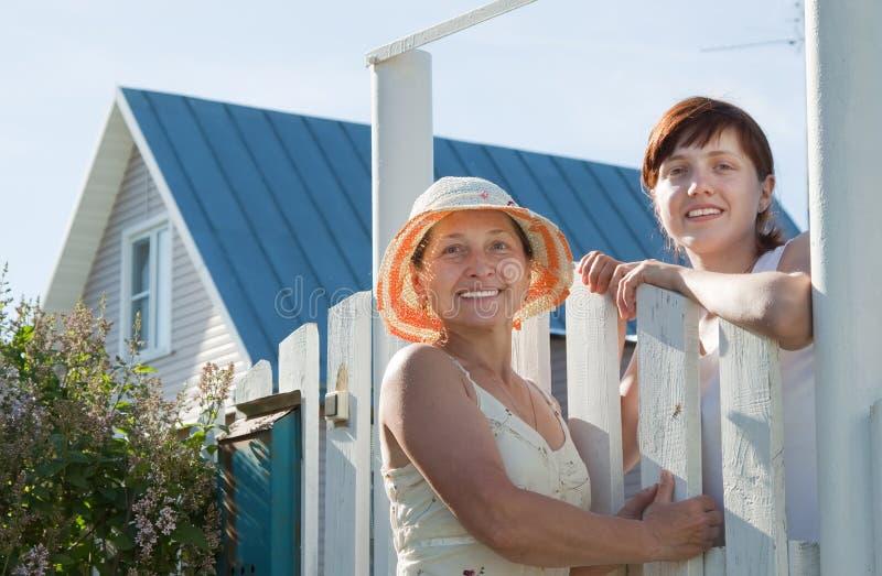 Dwa kobiet pobliski płotowa furta obraz stock