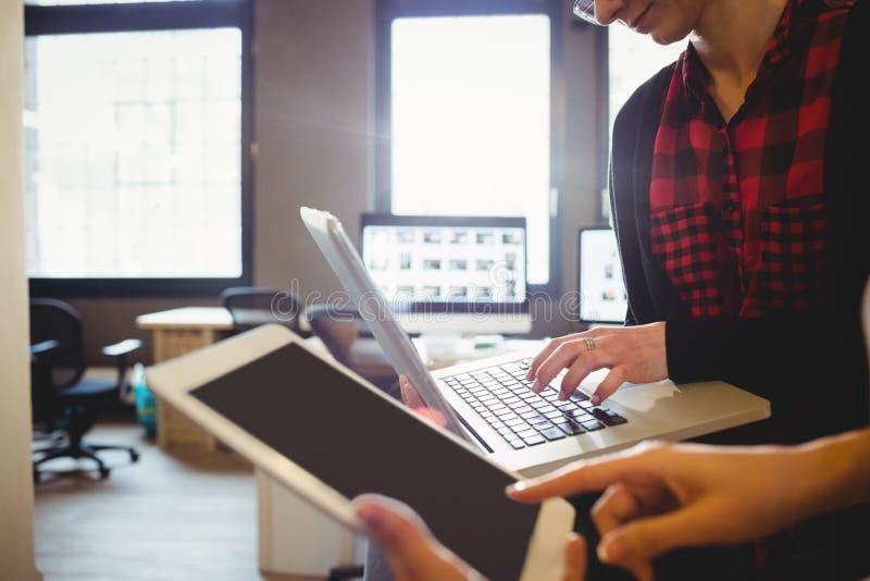 Dwa kobiet projektant grafik komputerowych używa cyfrową pastylkę i laptop obraz royalty free