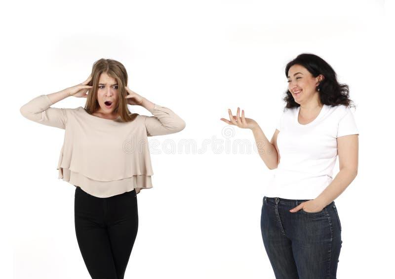 Dwa kobiet strzał z jeden kobietą śmia się innym kobietom i robi zabawie i jest w szoku i obraża Styl życia fotografia na białym  obrazy stock