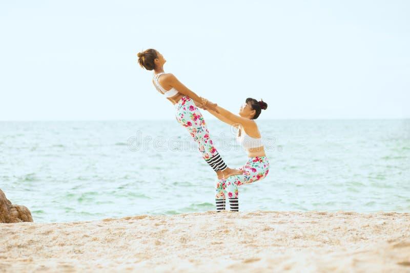 Dwa kobieta bawi? si? joga poz? na morze pla?y zdjęcia royalty free