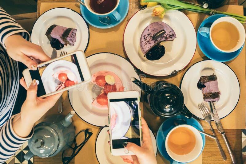 Dwa kobieta bierze mobilne fotografie stołowy fuul desery i herbata Odgórny widok Karmowi bloggers obrazy stock