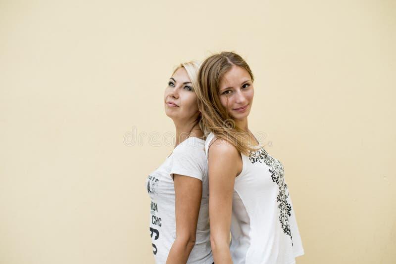Dwa kobieta przyjaciela pięknej brunetka i blondynka trwanie, z powrotem popierać, relaksują cieszą się obrazy stock