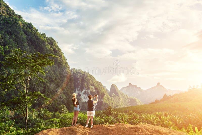 Dwa kobieta stoi przeciw dżungli krajobrazowego i chmurnego nieba tłu z kopii przestrzenią zdjęcia royalty free