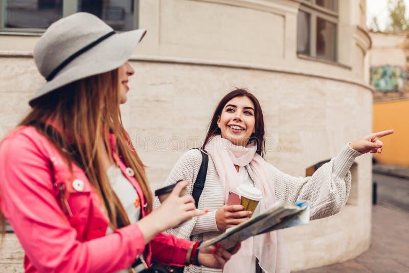 Dwa kobieta turysty szuka dla prawego sposobu używać mapę na miasto ulicie Szczęśliwy przyjaciół podróżników wskazywać obraz royalty free