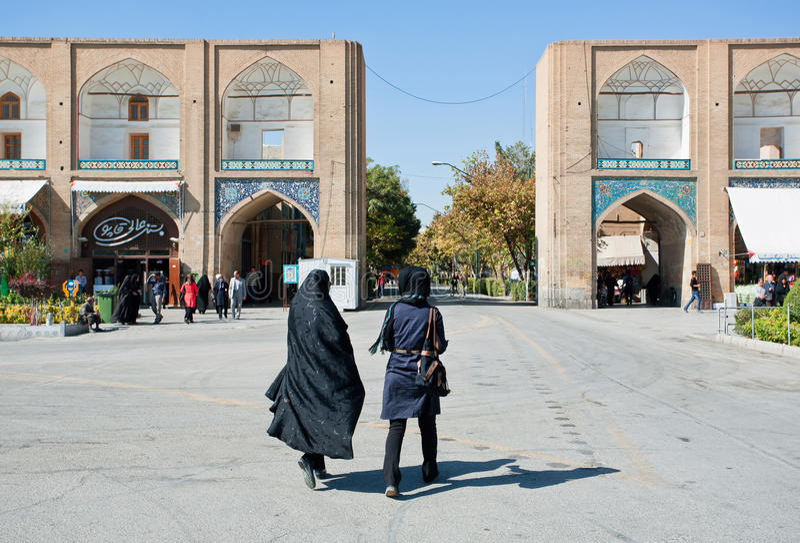 Dwa kobiety śpieszy się od imama w tradycyjnych hijabs Obciosują z starym bazarem zdjęcia stock