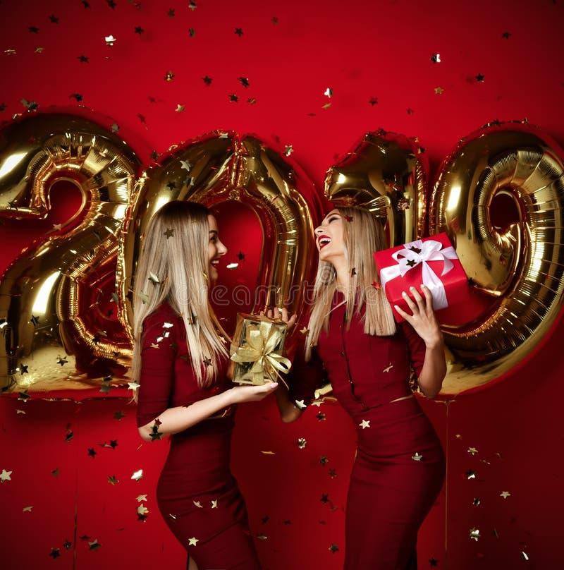 Dwa kobiety świętuje przy nowego roku przyjęcia szczęśliwymi roześmianymi dziewczynami w przypadkowych sukni rzutu złota gwiazd c zdjęcia royalty free