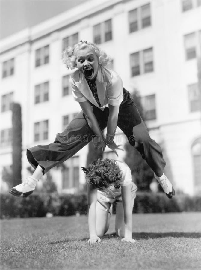 Dwa kobiety bawić się skok żaby wpólnie (Wszystkie persons przedstawiający no są długiego utrzymania i żadny nieruchomość istniej zdjęcie stock