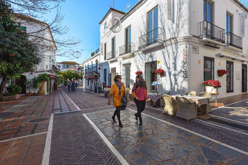 Dwa kobiety chodzą wzdłuż pięknej ulicy z z domami obrazy stock