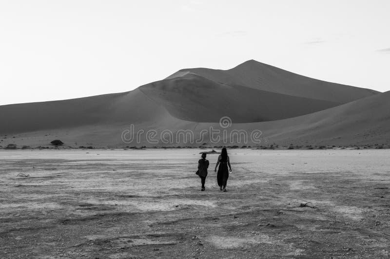 Dwa kobiety Chodzi przed Dużą ojczulek diuną przy świtem zdjęcia royalty free