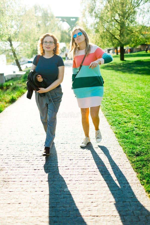 Dwa kobiety chodzi wzdłuż nabrzeża - cienie fotografia stock
