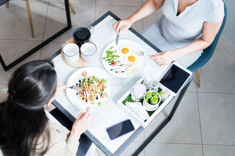 Dwa kobiety Cieszy się posiłek w kawiarni obraz royalty free