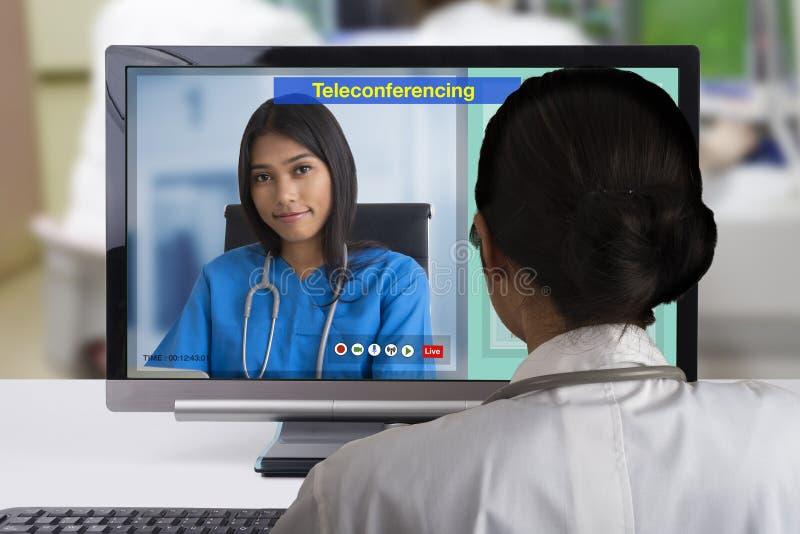 Dwa kobiety fabrykują używać telekonferencja technologię discutsion o cierpliwej skrzynce obrazy stock