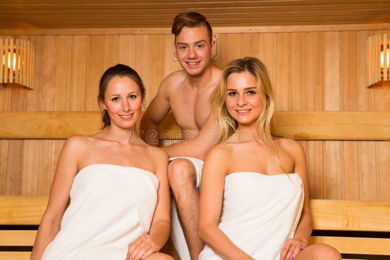 Dwa kobiety i jeden mężczyzna pozuje w sauna obraz royalty free