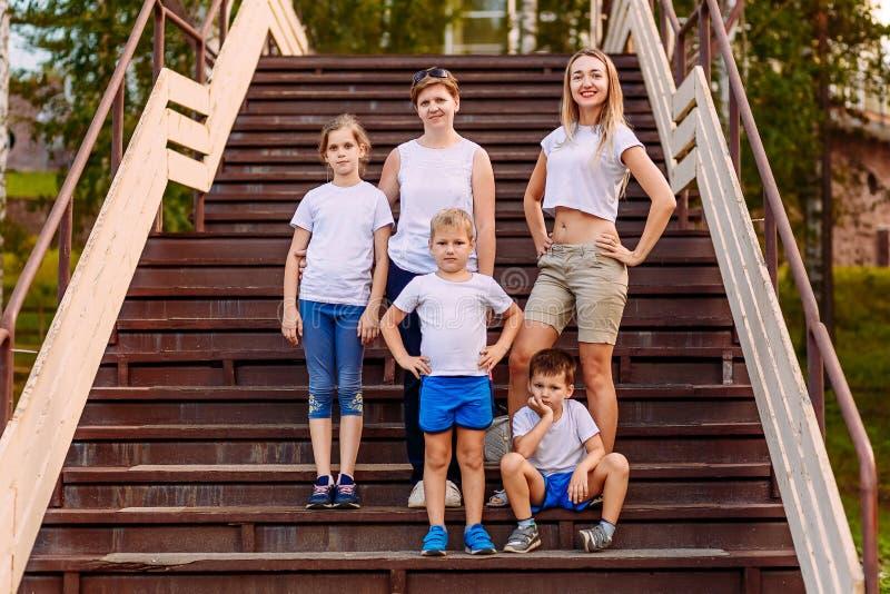 Dwa kobiety i trzy dziecka w pełnym przyroscie w białym koszulka stojaku na drabinie w lecie zdjęcie stock