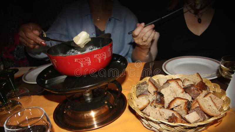 Dwa kobiety je serowego fondue stołem w kawiarni zdjęcie royalty free
