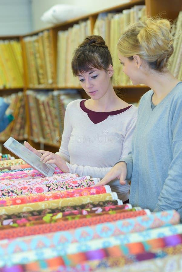 Dwa kobiety kupuje tkaninę w sklepie detalicznym obraz royalty free