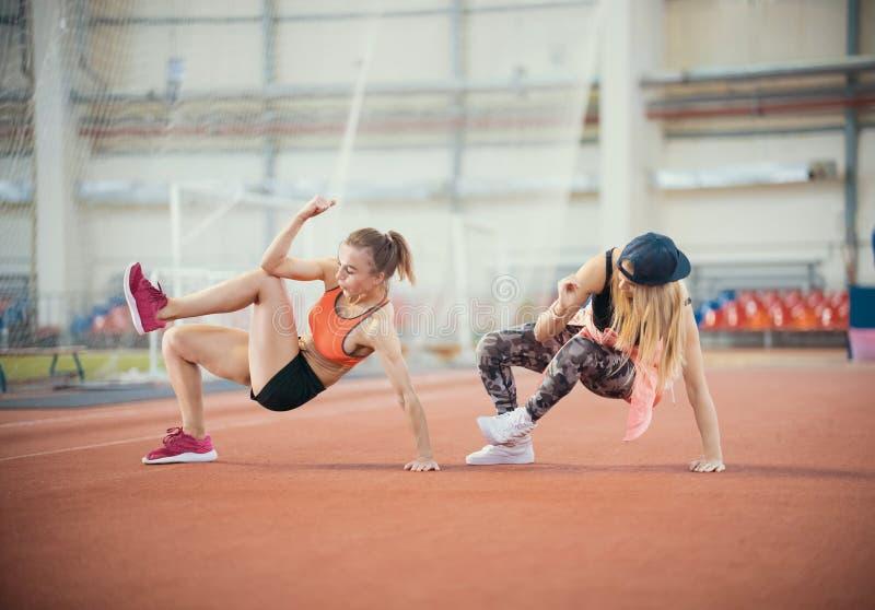 Dwa kobiety młody sportowy opracowywać Synchronously robi ruchy zdjęcia royalty free