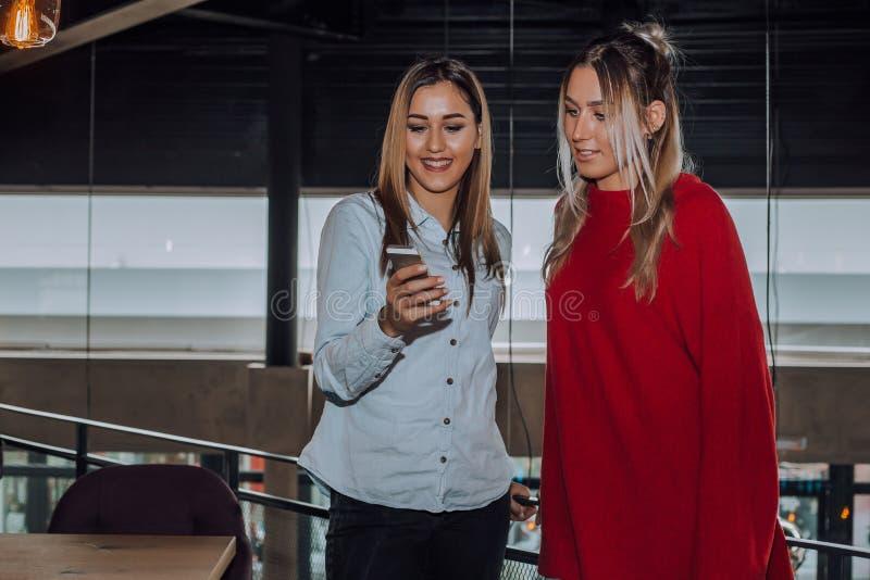 Dwa kobiety ma zabawę przy kawiarnią i patrzeje mądrze phon fotografia royalty free