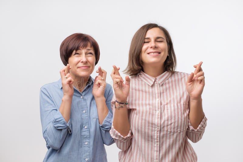 Dwa kobiety matka i skrzyżowanie córka palców i życzyć na dobre szczęście obrazy royalty free
