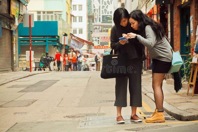 Dwa kobiety ogląda telefon komórkowego znajdować sposób w dużym mieście zdjęcie royalty free