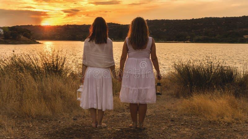 Dwa kobiety ogląda zmierzch z bielu lampionem i suknią obrazy royalty free