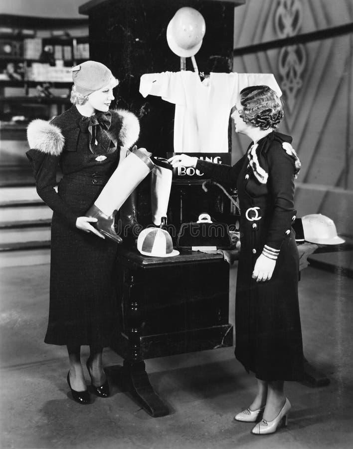 Dwa kobiety patrzeje pokazu w sklepie (Wszystkie persons przedstawiający no są długiego utrzymania i żadny nieruchomość istnieje  fotografia stock
