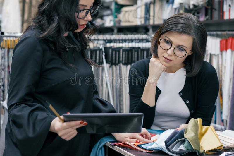 Dwa kobiety pracuje z wewnętrznych tkanin cyfrową pastylką w sali wystawowej dla zasłoien, tapicerowanie tkaniny, projektant i na fotografia stock
