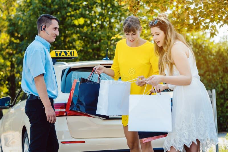 Dwa kobiety przychodzi od zakupy one potykają się używać taxi fotografia royalty free
