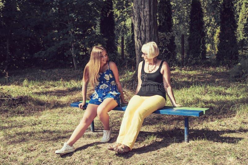 Download Dwa Kobiety Różni Pokolenia Siedzi Na Opowiadać I ławce Obraz Stock - Obraz złożonej z zdrowy, dorosły: 53785063